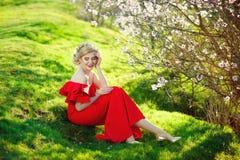 Goce alegre hermoso de la muchacha adolescente sobre fondo floreciente del árbol del albaricoque de la primavera foto de archivo