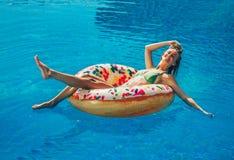 Goce de la mujer del bronceado en bikini en el colchón inflable en la piscina imagenes de archivo