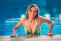 Goce de la mujer del bronceado en bikini en la piscina imagen de archivo