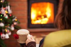 Goce de un café del latte por la chimenea en el tiempo de la Navidad Imágenes de archivo libres de regalías