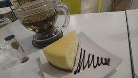Goce de un pastel de queso agradable del pedazo con infusión de hierbas fotos de archivo