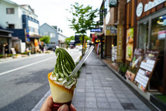 Goce del cono suave del servicio del helado de la leche con el prisionero de guerra de la escama del té verde Imagen de archivo libre de regalías