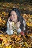 Goce en otoño y el hablar en el teléfono móvil Fotos de archivo