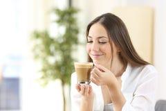 Goce feliz de la mujer de una taza de café con leche Imagenes de archivo