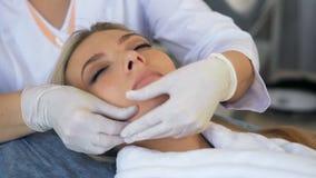 Goce hermoso de la mujer del masaje facial en salón de belleza almacen de metraje de vídeo