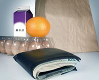 Goceries. Groceries cost with eggs milk paper bag money in wallet Royalty Free Stock Image