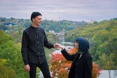 Gocka pary historia miłosna Mężczyzna i błękitna włosiana dziewczyna przy czerni ubraniami przy zielonym rzecznym tłem Obraz Stock