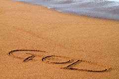 God. The word God written on the beach in sand Stock Photo