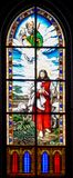 God above Jesus in a stained glass window. Jesus holding a lamb with god above in a stained glass window Royalty Free Stock Photos