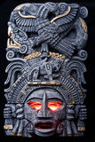 The god is angry. Aztec / Mayan god idol with glowing red eyes on a black background, angry appearance Royalty Free Stock Photo