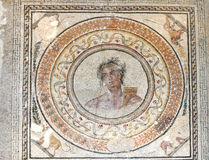 God Apollo. Second Century Ancient roman floor mosaic of Apollo (god of sun, light, truth, healing and prophesy), in a laurel wreath medallion frame with 4 lions Royalty Free Stock Photo