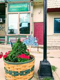 God Bless America in Flower Pot. Patriotic sign on rural Street side with cobbler storefront in background. Americana Stock Photo