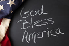 God Bless America sign. A God Bless America sign with vintage American flag on a chalkboard Royalty Free Stock Images