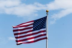 God Bless the American Flag. American flag fluttering in the blue sky, Provincetown, MA Stock Image