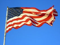 God Bless The USA!. The American flag flies strong and proud against an afternoon sky. The slanting rays of the sun just touch the flag with hints of gold amidst Royalty Free Stock Photo
