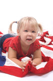God Bless USA. Adorable little blond girl laying on an American flag smiling Royalty Free Stock Image