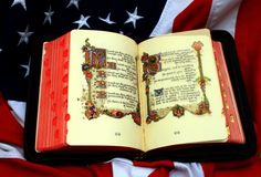 God and country 4. Open bible on American flag showing stars and bars Royalty Free Stock Image