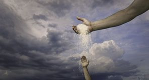 God Hand Pouring Out Blessing. Through White Clouds Towards Hand of Man royalty free stock photography