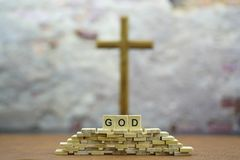 God letters with blur holy cross on leather table and concrete wall background. God letters with defocus holy cross on leather sheet and concrete wall royalty free stock photos