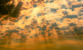 God light. Dramatic dark cloudy sky with sun beam. Yellow sun rays through dark and white clouds. God light from heaven for hope stock photo