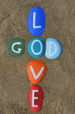 God is love, multicolored stones composition. Love is God and God is love, message on colourful stones over the sand Royalty Free Stock Image