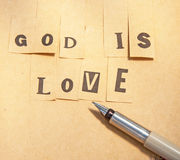 God is love. Text God is love created with letters taken from various fonts stuck to a post-it style note and with a fountain pen beside stock photos
