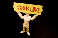 GOD IS LOVE. Wooden model show God is love in darkness Royalty Free Stock Images