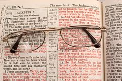 And God So Loved the World. Glasses laying on a Bible with the lenses highlighting one of the most famous verses of the Bible Royalty Free Stock Image