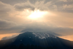 God rays. During sunset over mountain silhouette Royalty Free Stock Image