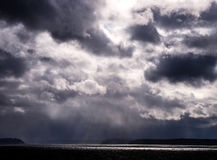 God Rays, Storm Clouds that resemble a face (top right). Dark ominous clouds with rays of light falling onto the Puget Sound Royalty Free Stock Images