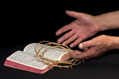 God's Grace. Open Bible with rugged hands and crown of thorns smbolic to God's Grace royalty free stock photo