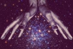 God& x27; s Hände unten, die eine Sterngalaxie im Raum halten Stockbild