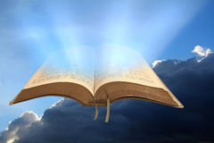 God`s kingdom rules open bible. Photo of open holy bible set against a stormy cloud sky with sun rays shining through pages Stock Images