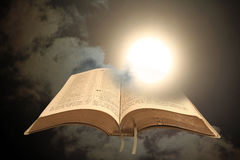 God`s revelation to mankind. Concept photo of an open holy bible set against the sun shining through a stormy black sky depicting spiritual enlightenment Royalty Free Stock Photo