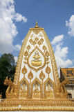 God salute sculpture on white and pagoda surface. Ornament: god salute sculpture on white and gold pagoda surface against blue sky at wat Phrathat Nong Bua in Stock Photo