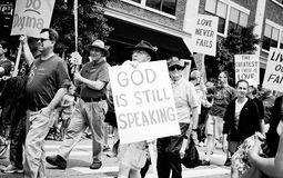 A man carries a sign about God during Gay Pride in. Des Moines Gay Pride Parade royalty free stock photos