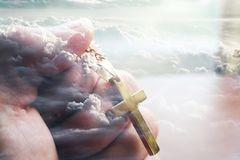In God We Trust. With gold cross in hand with clouds representing heaven royalty free stock photography
