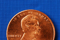 In God We Trust from the penny. Isolated on blue Royalty Free Stock Image