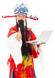 God of wealth holding a laptop and thumb up Stock Photo