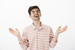 God what next. Portrait of sarcastic laughing boyfriend in stripes shirt, raising hands up and looking at sky with smile. Seeing something hilarious and Royalty Free Stock Images