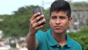 Goda som ser den tonåriga pojken som tar Selfy Royaltyfri Bild