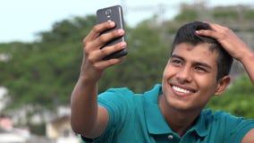 Goda som ser den tonåriga pojken som tar Selfy och att le Arkivbilder