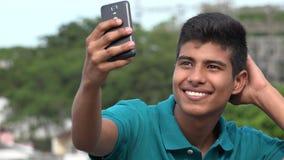 Goda som ser den tonåriga pojken som tar Selfy och att le Royaltyfria Bilder