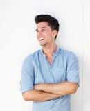 Goda som ser den unga mannen som ler med korsade armar Fotografering för Bildbyråer