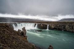 Godafoss waterfall near Akureyri in the Icelandic highlands. Dramatic clouds and snow covered mountains in the back.