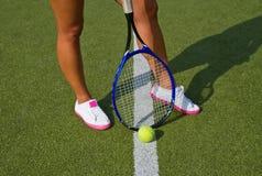 Godan lägger benen på ryggen sportställningar med racket på domstolen på den soliga sommardagen Arkivfoton