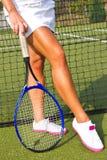 Godan lägger benen på ryggen ställningar med racket på domstolen på den soliga sommardagen Arkivfoto