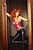 Goddes of Rock. Red-haired girl wearing corset and leather pants Royalty Free Stock Photo
