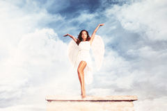 Goddess. Beautiful goddess like young brunette woman  with angel wings and white dress against sky with clouds , full body shot, outdoor Stock Photo