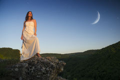 The Goddess. Beautiful young woman wearing elegant white dress standing on a rock overlooking the great expance of forests and mountains under blue sky with moon Royalty Free Stock Image